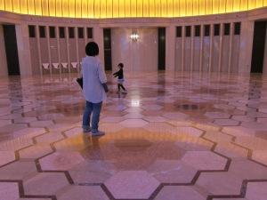 Child dancing in the rotunda between escalators